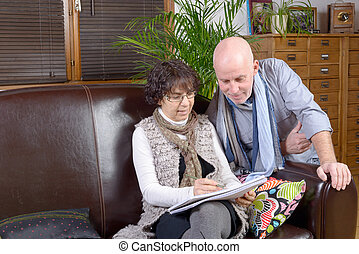 mature couple looking at a note book