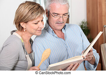 Mature couple looking at a recipe book