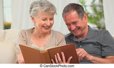 Cute mature couple looking at an album