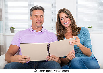 Mature Couple Looking At Photo Album