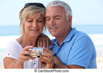 Mature couple looking at the photos on their digital camera