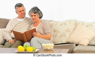 Mature couple looking at their albu
