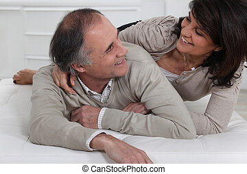 Mature couple lying on a bed