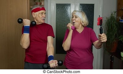 Mature couple man and woman fitness trainer coach records video online workout course with a smartphone live streaming sport exercises at home. Senior old grandmother and grandfather live stream, blog