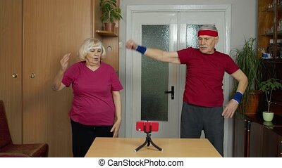 Mature couple man and woman fitness trainer coach records video online workout course with a smartphone live streaming sport exercises at home. Senior grandmother and grandfather live stream, blog