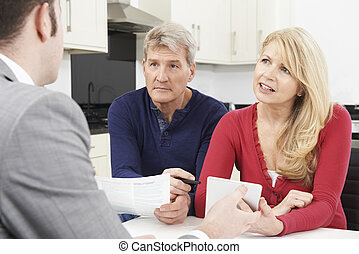 Mature Couple Meeting With Financial Advisor At Home
