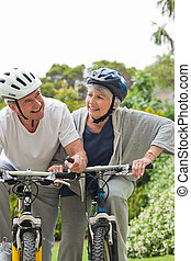 Mature couple mountain biking outsi