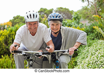 Mature couple mountain biking outside