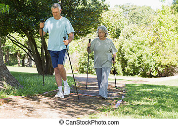 Mature couple Nordic walking at park - Full length of a...