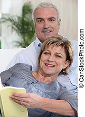 Mature couple on a sofa reading a book