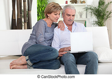 Mature couple on sofa with computer