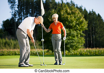 Mature or senior couple playing golf, he is putting at the green