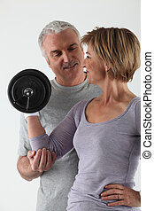 Mature couple practicing fitness on white background