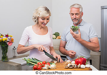 Mature couple preparing food togeth