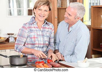 Mature couple preparing vegetables
