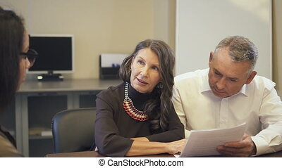 Mature couple reading and discussing mortgage contract in real estate agency.