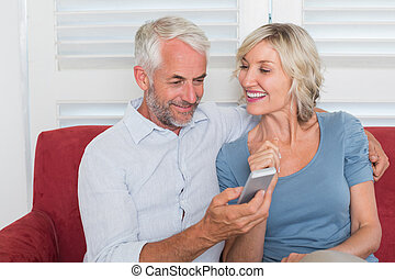 Mature couple reading text message - Smiling mature couple...