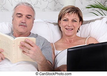 Mature couple relaxing in bed