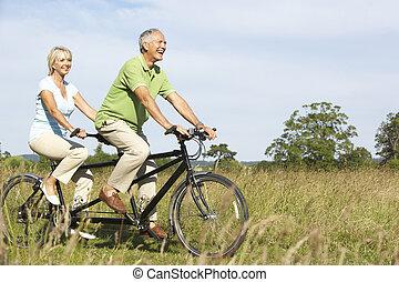 Mature couple riding tandem