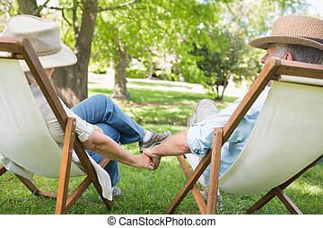 Mature couple sitting in deck chairs at park - Rear view of ...