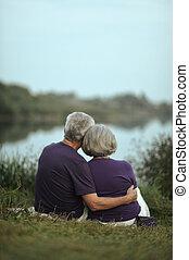 sitting near lake - Mature couple sitting near lake back...