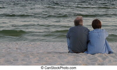 Mature couple sit in the sand at the beach watching the waves roll to shore at dusk.