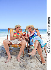 Mature couple sitting on deck chair