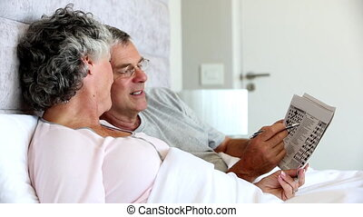 Mature couple solving crossword in