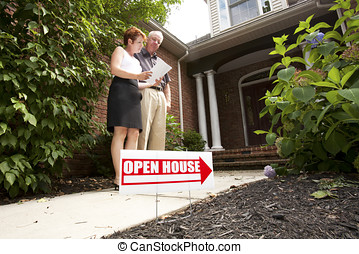 Mature couple standing in front of a house with an Open House sign looking at documents
