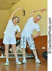 Mature couple stretching in gym