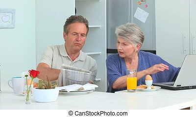 Mature couple talking during the morning in the kitchen