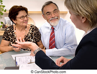 Mature couple talking to financial planner at home