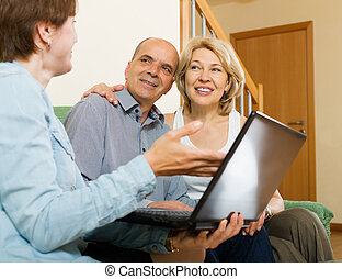 Mature couple talking with employee with laptop