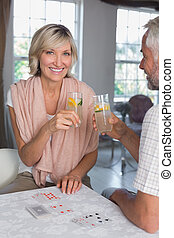 Mature couple toasting drinks while