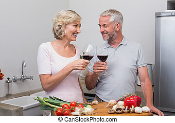 Mature couple toasting wine glasses in kitchen