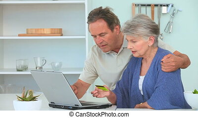 Mature couple using a credit card to pay something on...