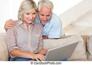 Mature couple using laptop on sofa