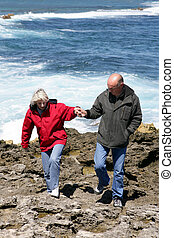 Mature couple walking along a rocky coast