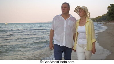 Mature couple walking along seaside - Steadicam shot of a...