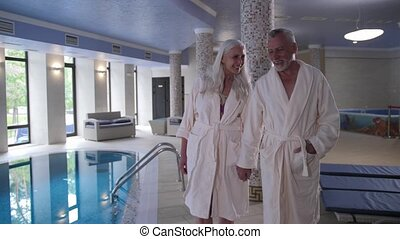 Mature couple walking hand in hand to hotel pool