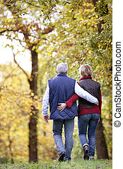 Mature couple walking through the woods