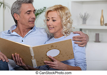 Mature couple watching a photo-album