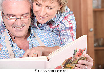 Mature couple with a cookbook