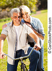 mature couple with bike outdoors