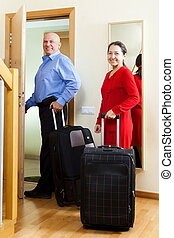 mature couple with luggage in home