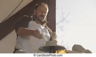 Mature craftsman labors on creation of clay dish.