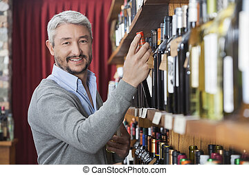 Mature Customer Choosing Wine Bottle In Store