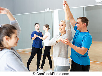 Mature dancing couple during group class - Smiling middle ...