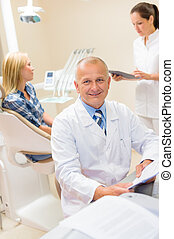 Mature dentist surgeon at office with patient
