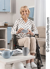 Mature disabled woman holding phone